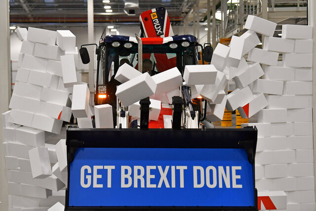FILE - In this Tuesday Dec. 10, 2019 file photo, Britain's Prime Minister Boris Johnson drives a JCB through a symbolic wall with the Conservative Party slogan 'Get Brexit Done' in the digger bucket, during an election campaign event at the JCB manufacturing facility in Uttoxeter, England. Johnson's Conservatives won an overwhelming majority in the election two days later and Britain is now scheduled to leave the European Union on Jan. 31, 2020. (Ben Stansall/Pool via AP)