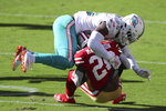 FILE - In this Oct. 11, 2020, file photo,Miami Dolphins outside linebacker Jerome Baker (55) tackles San Francisco 49ers running back Jerick McKinnon during the second half of an NFL football game in Santa Clara, Calif. Twelve months ago, they were 0-7 under first-year coach Brian Flores and allowing 34.0 points a game, and they went on to surrender the most points in franchise history. They've gone from worst to first in the NFL, and are now giving up 18.6 points per game. (AP Photo/Jed Jacobsohn, File)