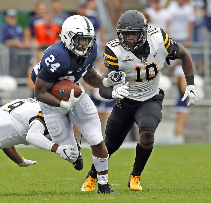 Penn State's Miles Sanders (24) evades a tackle by Appalachian State's Austin Exford (9) and Tim Frizzell (10) during the first half of an NCAA college football game in State College, Pa., Saturday, Sept. 1, 2018. (AP Photo/Chris Knight)