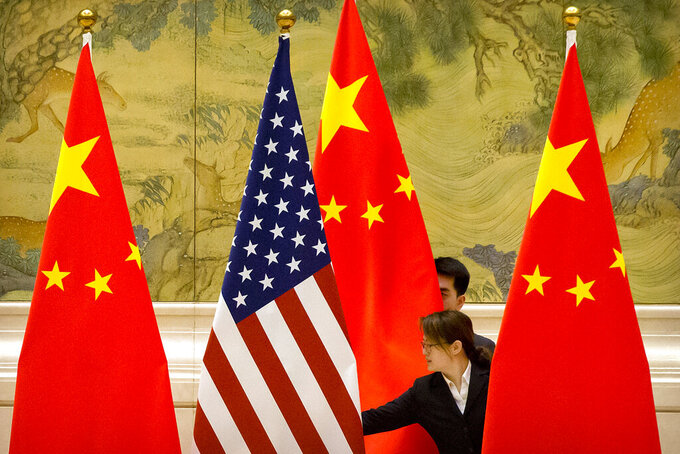 FILE - In this Feb. 14, 2019 file photo, Chinese staffers adjust the U.S. and Chinese flags before the opening session of trade negotiations between U.S. and Chinese trade representatives at the Diaoyutai State Guesthouse in Beijing. New polling from the Pew Research Center shows strong negative attitudes among Americans toward China, with almost nine out of 10 adults seeing the country as hostile or a danger to U.S. interests. (AP Photo/Mark Schiefelbein, File)