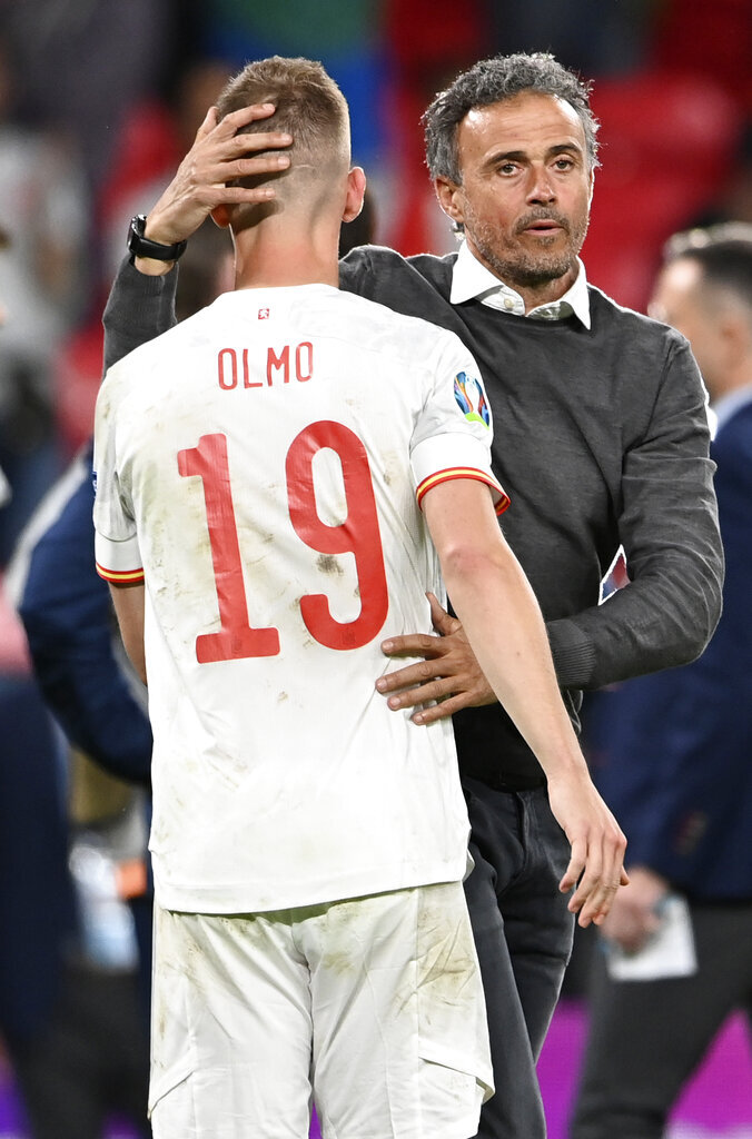 Spain's manager Luis Enrique , right, comforts Spain's Dani Olmo after the Euro 2020 soccer championship semifinal match between Italy and Spain at Wembley Stadium in London, Tuesday, July 6, 2021. (Andy Rain/Pool via AP)