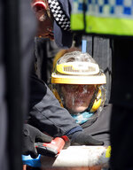 A police office tries to unchain a protestor with power tools at Oxford Circus in London, Friday, April 19, 2019. The group Extinction Rebellion is calling for a week of civil disobedience against what it says is the failure to tackle the causes of climate change. (AP Photo/Frank Augstein)