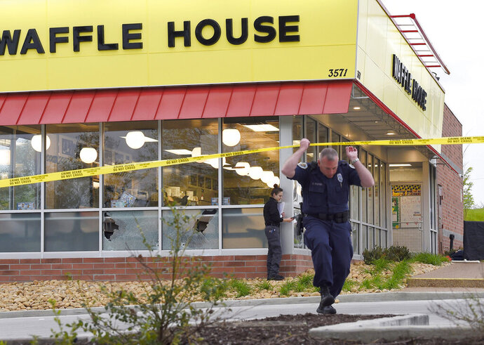 FILE- In this April 22, 2018 file photo, law enforcement officials work the scene of a fatal shooting at a Waffle House in the Antioch neighborhood of Nashville, Tenn. The father of the man accused of killing four people at the Waffle House in Tennessee last year pleaded not guilty Thursday, April 25, 2019, to charges related to the gun used in the shooting. Jeffrey Reinking is accused of giving an AR-15-style rifle to his 30-year-old son, Travis Reinking, who authorities said used it in Nashville on April 22, 2018. (George Walker IV/The Tennessean via AP, File)