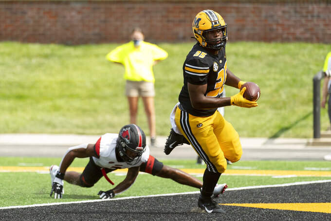 Missouri running back Michael Cox, right, scores a touchdown in front of Southeast Missouri State safety Louis Taylor III, left, during the fourth quarter of an NCAA college football game Saturday, Sept. 18, 2021, in Columbia, Mo. Missouri won 59-28. (AP Photo/L.G. Patterson)