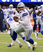 FILE - In this Dec. 30, 2018, file photo, Dallas Cowboys quarterback Dak Prescott looks to hand off during the first half of an NFL football game against the New York Giants, in East Rutherford, N.J. Russell Wilson won a playoff game with Seattle as a rookie, a Super Bowl in his second season and another NFC championship the third time around. The best Dak Prescott can hope for with the Dallas Cowboys is to join Wilson on that list of Super Bowl winners in his third year, a quest that will start with the first postseason meeting of quarterbacks with quite a bit in common, other than postseason pedigree.(AP Photo/Bill Kostroun, File)