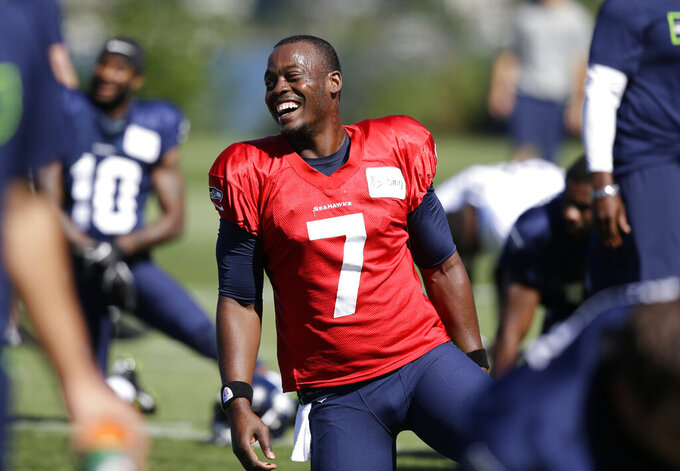 "FILE - In this July 27, 2014, file photo, Seattle Seahawks quarterback Tarvaris Jackson smiles while stretching at an NFL football camp practice in Renton, Wash. Former NFL quarterback Tarvaris Jackson has died in a one-car crash outside Montgomery, Ala., authorities said Monday, April 13, 2020. He was 36. The 2012 Chevrolet Camaro that Jackson was driving went off the road, struck a tree and overturned at 8:50 p.m. Sunday, Trooper Benjamin ""Michael"" Carswell, an Alabama Law Enforcement Agency spokesman, said in a news release. Jackson was pronounced dead at a hospital. (AP Photo/Elaine Thompson, File)"