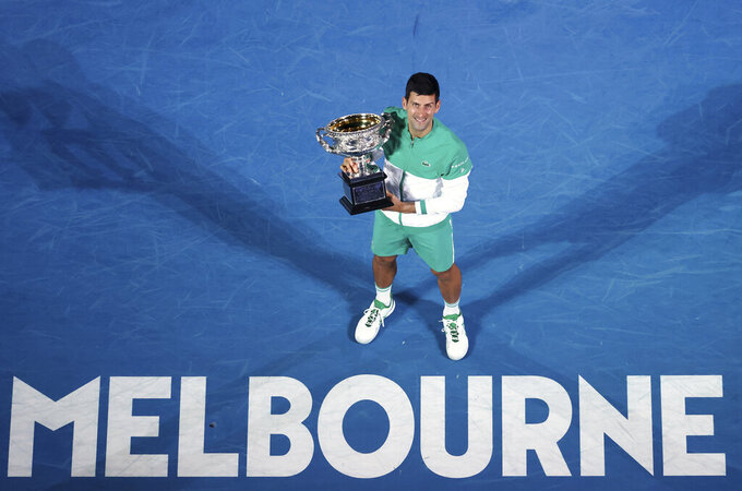 FILE - Feb. 21, 2021, file photo Serbia's Novak Djokovic holds the Norman Brookes Challenge Cup after defeating Russia's Daniil Medvedev in the men's singles final at the Australian Open tennis championship in Melbourne, Australia. Players who haven't received a COVID-19 vaccination are unlikely to get a visa to enter the country for the Australian Open next January, according to the political leader of the state which hosts the season-opening major. (AP Photo/Hamish Blair, File)