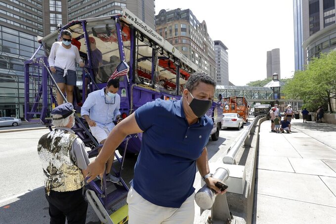 Sightseers disembark following a ride on one of the iconic duck boats after tours resumed, Monday, July 13, 2020, in Boston as Phase 3 of the city's coronavirus economic restart began. Museums, movie theaters, historical sites and gyms in Boston were permitted to reopen Monday with certain restrictions, a week after most of the rest of Massachusetts. (AP Photo/Steven Senne)