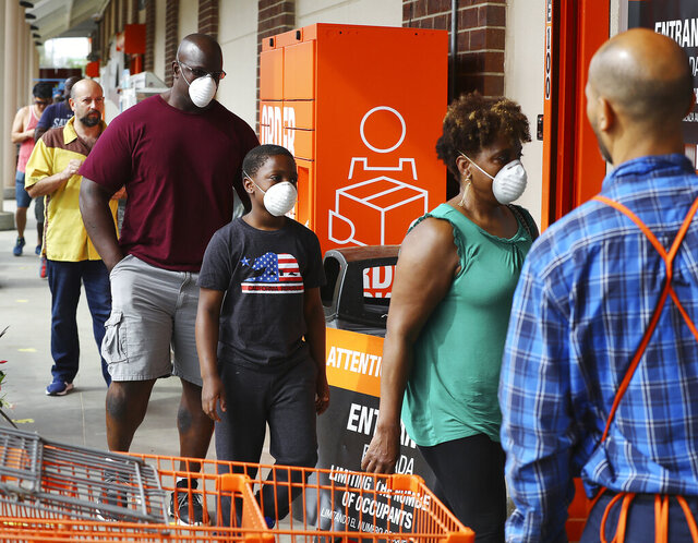 Customers wait in line to enter the Home Depot store at Midtown Place while the store limits the number of occupants to maintain six feet of space between shoppers and help prevent the spread of coronavirus on Sunday, March 29, 2020, in Atlanta. (Curtis Compton//Atlanta Journal-Constitution via AP)