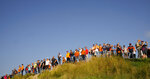 The so-called Orange Army, fans of Red Bull driver Max Verstappen of the Netherlands line the top of a dune to watch the first free practice ahead of Sunday's Formula One Dutch Grand Prix at the Zandvoort racetrack, Netherlands, Friday, Sept. 3, 2021. (AP Photo/Francisco Seco)