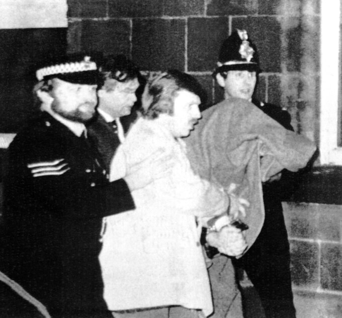 """FILE - This Jan. 5, 1981 file photos shows Peter William Sutcliffe, 35, under a blanket at right, being led from Dewsbury Magistrates Court in Dewsbury by police officers. On Friday, Nov. 13, 2020, Britain's Prison Service said that serial killer Peter Sutcliffe _ known as the """"Yorkshire Ripper"""" died in the hospital. Sutcliffe was serving a life sentence after being convicted of murdering 13 women in northern England between 1975 and 1980. (AP Photo/Pyne, file)"""