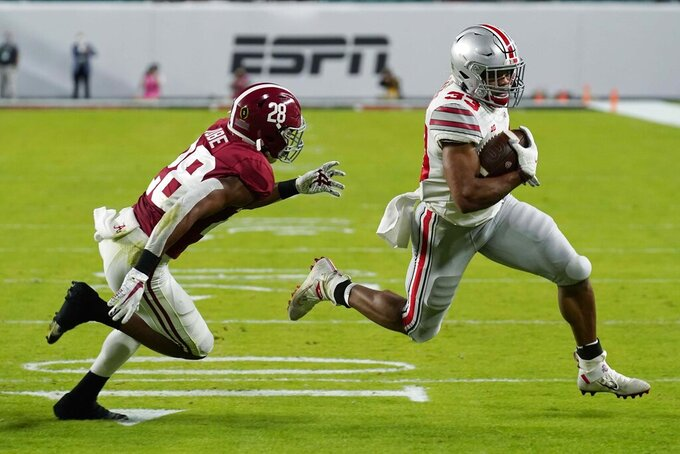 Ohio State running back Master Teague III runs for touchdown past Alabama defensive back Josh Jobe during the first half of an NCAA College Football Playoff national championship game, Monday, Jan. 11, 2021, in Miami Gardens, Fla. (AP Photo/Chris O'Meara)