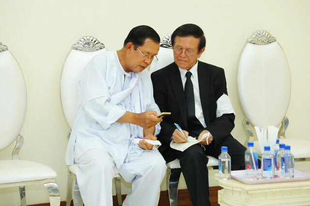 Cambodian Prime Minister Hun Sen, left, talks with dissolved main opposition Cambodia National Rescue Party leader Kem Sokha at the mourning ceremony of Sen's mother in-law, in Phnom Penh, Cambodia, Tuesday, May 5, 2020. Cambodian Prime Minister Hun Sen met Tuesday with an opposition leader whose political party was dissolved after he was charged with treason. (Pool via AP)