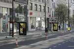 FILE  - In this Tuesday, March 24, 2020 file photo, a woman wearing a face mask to protect against coronavirus, waits at a bus stop on a deserted Oxford Street in London. Unemployment across the U.K. has held steady during the coronavirus lockdown as a result of a government salary support scheme, but there are clear signals emerging that job losses will skyrocket over coming months. The Office for National Statistics said Thursday, July 16, 2020 there were 649,000 fewer people, or 2.2%, on payroll in June when compared with March when the lockdown restrictions were imposed.  (AP Photo/Matt Dunham, File)