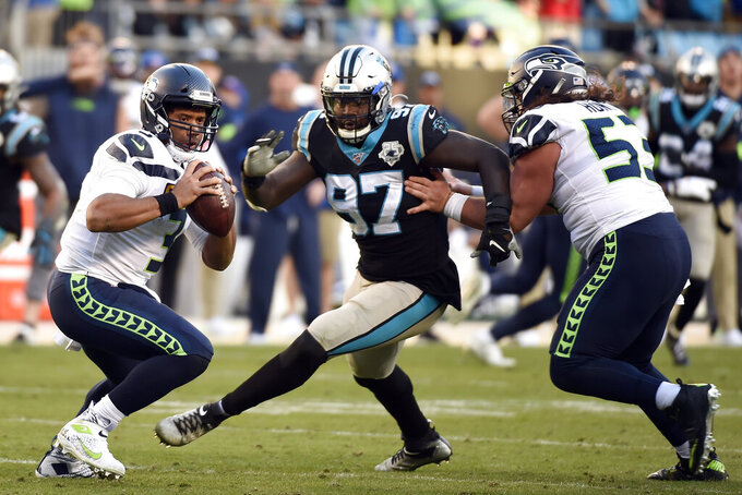 FILE - In this Dec. 15, 2019, file photo, Seattle Seahawks quarterback Russell Wilson (3) scrambles as Carolina Panthers linebacker Mario Addison (97) rushes during the second half of an NFL football game in Charlotte, N.C. The Panthers will look to upgrade their defense in the NFL draft after losing nine starters from last year's unit, including five-time All-Pro linebacker Luke Kuechly. Edge rusher Addison and top cornerback James Bradberry left via free agency, while veteran safety Eric Reid was released. (AP Photo/Mike McCarn)
