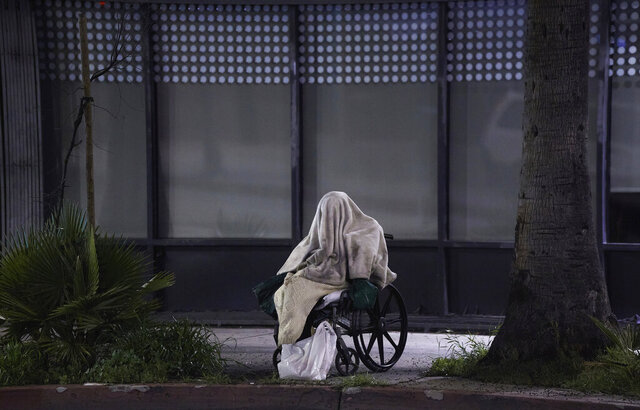 A homeless person sits on a wheelchair under rainy weather on Sunset Blvd., in the Echo Park neighborhood of Los Angeles Monday, April 6, 2020. One population is particularly vulnerable to contracting and spreading the coronavirus: the homeless. Officials have vowed repeatedly to get them indoors, but testing shortages and bureaucratic wrangling are making it difficult. Relatively few of California's 150,000 homeless population have been moved into individual quarters. It's unclear how many even have the highly contagious virus. It's a problem playing out nationwide and it's unclear how many may even have coronavirus. (AP Photo/Damian Dovarganes)
