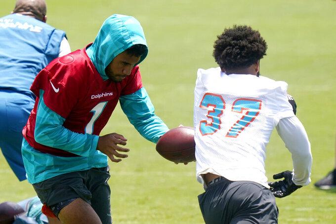Miami Dolphins quarterback Tua Tagovailoa (1) runs a drill with running back Myles Gaskin (37) at the team's NFL football training facility, Wednesday, May 26, 2021, in Davie, Fla. (AP Photo/Lynne Sladky)