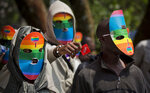 FILE---- In this file photo of Monday Feb. 10, 2014, Kenyan people who identify as gay and lesbian and others supporting their cause, wear masks to preserve their anonymity and one holds out a wrapped condom, as they stage a rare protest in Nairobi, Kenya.  Extortion, human rights violations ranging from assaults, physical, sexual and verbal, denial of access to state services, forceful evictions, harassment, being disowned by family members among other challenges, may become a thing of the past for the Kenyan gay community if a court rules on Friday Feb. 22, 2019, in their favour to abolish laws that criminalize homosexual behaviour. (AP Photo/Ben Curtis-File)