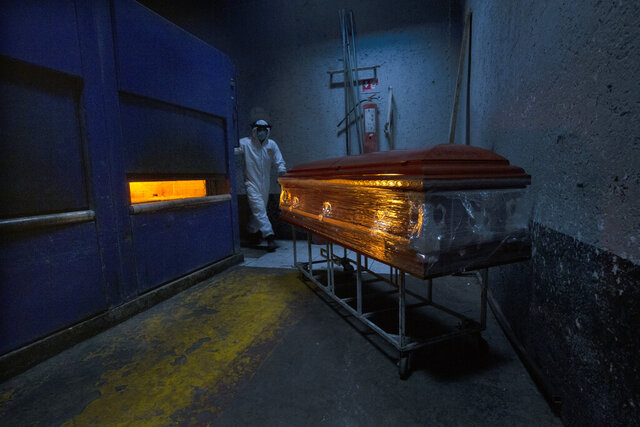 A crematorium worker prepares an oven for a COVID-19 victim at the Panteón de San Nicolás Tolentino cemetery in the Iztapalapa neighborhood of Mexico City, Thursday, June 4, 2020. Funeral parlors and crematoriums in Iztapalapa, a borough of 2 million people, say they have seen their work multiplied with the surging number of dead of COVID-19 in the capital's hardest-hit corner by the new coronavirus. (AP Photo/Marco Ugarte)