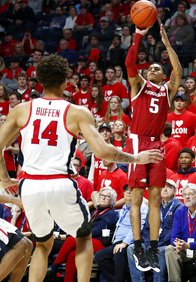 Arkansas guard Jalen Harris (5) attempts a shot while Mississippi forward KJ Buffen (14) steps up during the second half of the NCAA college basketball game in Oxford, Miss., Saturday, Jan. 19, 2019. Mississippi won 84-67. (AP Photo/Rogelio V. Solis)