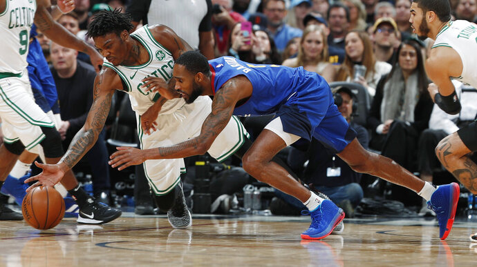 Boston Celtics center Robert Williams III, left and Denver Nuggets guard Will Barton reach for the ball during the second half of an NBA basketball game Friday, Nov. 22, 2019, in Denver. The Nuggets won 96-92. (AP Photo/David Zalubowski)