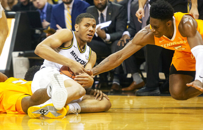 Missouri's Javon Pickett, left, holds onto the ball as Tennessee's Admiral Schofield, right, moves toward him during the first half of an NCAA college basketball game Tuesday, Jan. 8, 2019, in Columbia, Mo. (AP Photo/L.G. Patterson)