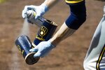 A batboy sprays disinfectant on some bat doughnuts during the seventh inning of a baseball game between the Milwaukee Brewers and the Chicago White Sox Monday, Aug. 3, 2020, in Milwaukee. (AP Photo/Morry Gash)