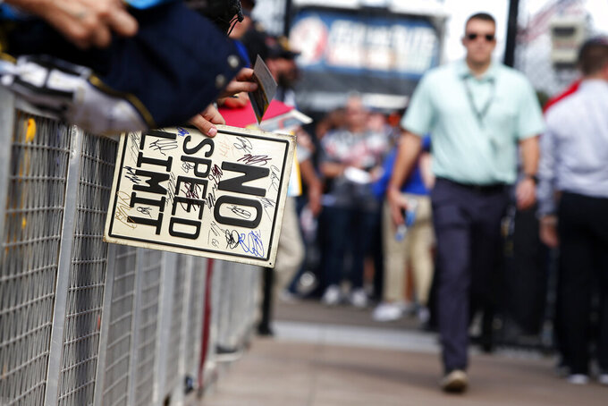 A race fan waits to have his sign autographed by drivers prior to a NASCAR Cup Series auto race at ISM Raceway, Sunday, Nov. 10, 2019, in Avondale, Ariz. (AP Photo/Ralph Freso)