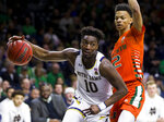 Notre Dame's Temple 'T.J.' Gibbs (10) drives in next to Miami's Isaiah Wong (2) during the second half of an NCAA college basketball game Sunday, Feb. 23, 2020, in South Bend, Ind. (AP Photo/Robert Franklin)