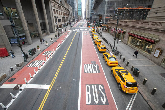 Yellow cabs line an empty 42nd St. waiting for fares outside Grand Central Terminal, Wednesday, March 25, 2020, in New York. Hospitalizations from COVID-19 were rising faster than expected in New York as residents and leaders prepared for a peak in cases that is expected to still be weeks away. Temporary hospitals, and even a morgue in Manhattan, are being setup. (AP Photo/Mary Altaffer)