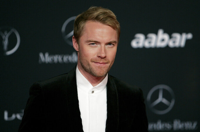 """FILE - In this Monday, Feb. 7, 2011 file photo, Irish singer Ronan Keating arrives for the Laureus Awards in Abu Dhabi, United Arab Emirates. Keating has accepted """"substantial damages"""" from a British tabloid newspaper publisher over phone hacking it was reported on Monday, July 26, 2021. The former member of boyband Boyzone is the latest in a long list of celebrities whose voicemail messages were intercepted by the News of the World more than a decade ago. Keating's lawyer told a High Court hearing that the singer had identified a number of """"suspicious"""" articles published between 1996 and 2011 which contained his private information. (AP Photo/Nousha Salimi, File)"""