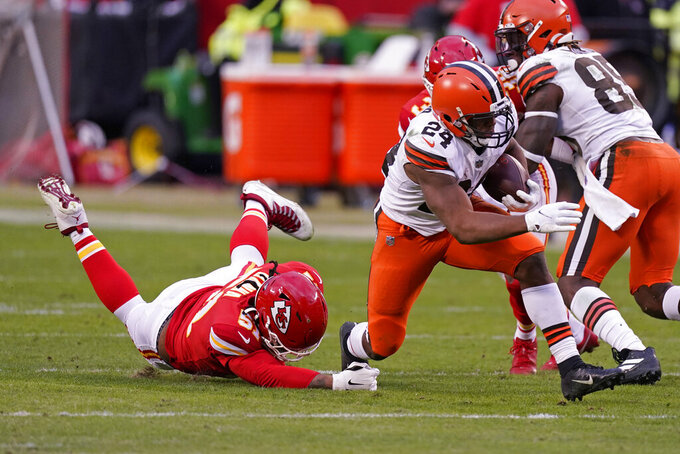 Cleveland Browns running back Nick Chubb (24) runs from Kansas City Chiefs defensive end Mike Danna, left, during the second half of an NFL divisional round football game, Sunday, Jan. 17, 2021, in Kansas City. (AP Photo/Charlie Riedel)