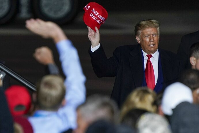 FILE - In this Sept. 17, 2020 file photo President Donald Trump throws a hat to the crowd after speaking at a campaign rally at the Central Wisconsin Airport in Mosinee, Wis. Hackers stole $2.3 million from the Wisconsin Republican Party's account that was being used to help reelect President Donald Trump in the key battleground state, the party's chairman told The Associated Press on Thursday, Oct. 29. (AP Photo/Morry Gash, File)