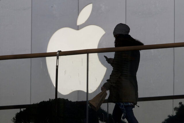 FILE - In this Dec. 23, 2013, file photo, a woman using a phone walks past Apple's logo near its retail outlet in Beijing. The FBI is asking Apple to help extract data from iPhones that belonged to the Saudi aviation student who fatally shot three sailors at a U.S. naval base in Florida in December 2019. (AP Photo/Ng Han Guan, File)