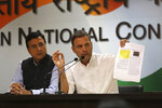 India's Congress party President Rahul Gandhi displays documents as he accuses Narendra Modi's government of buying 36 Rafale fighter jets from France's Dassault at a highly inflated price, in New Delhi, India, Thursday, Oct. 11, 2018. Gandhi also accused Modi's government of favoring the company owned by industrialist Anil Ambani, Reliance Group, when choosing an Indian partner for Dassault. India's defense minister is travelling to Paris amid controversy over the multi-billion dollar deal. (AP Photo)