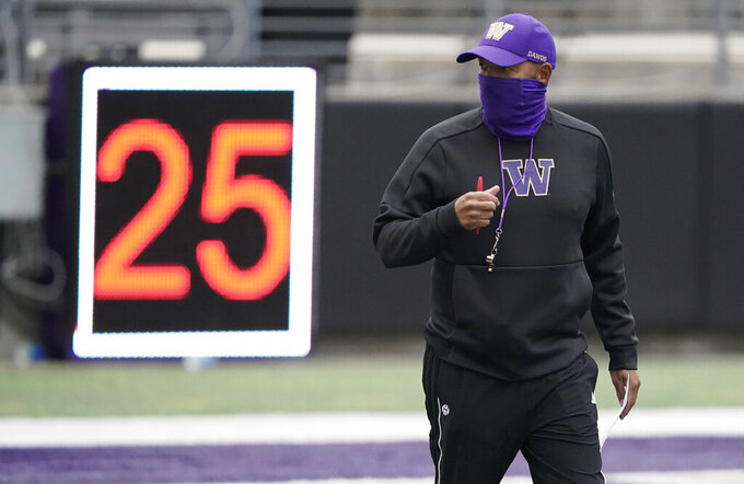 Washington head coach Jimmy Lake stands near a play clock during NCAA college football practice, Friday, Oct. 16, 2020, in Seattle. (AP Photo/Ted S. Warren)