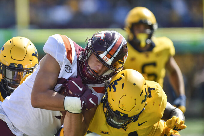 Virginia Tech tight end Drake DeIuliis (89) is tackled by West Virginia safety Alonzo Addae (4) during the second half of an NCAA college football game in Morgantown, W.Va., Saturday, Sep. 18, 2021. (AP Photo/William Wotring)