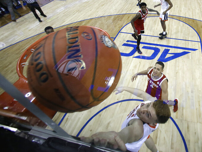 Virginia's Kyle Guy drives to the basket against North Carolina State's Jericole Hellems (4) during the first half of an NCAA college basketball game in the Atlantic Coast Conference men's tournament in Charlotte, N.C., Thursday, March 14, 2019. (AP Photo/Chuck Burton)
