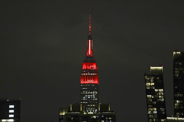 The Empire State building is lit in red and white lights to honor emergency medical workers Tuesday, March 31, 2020, in New York. The new coronavirus causes mild or moderate symptoms for most people, but for some, especially older adults and people with existing health problems, it can cause more severe illness or death. (AP Photo/Frank Franklin II)