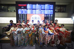 Kimono-clad employees of the Tokyo Stock Exchange and models pose for photographers in front of stock price boards after a ceremony marking the start of this year's trading in Tokyo Friday, Jan. 4, 2019. (AP Photo/Eugene Hoshiko)