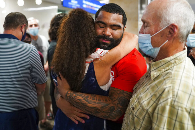 Olympic gold medal wrestler Gable Steveson hugs a fan as he is welcomed by family and fans after arriving at Minneapolis-Saint Paul International Airport on Sunday, Aug. 8, 2021, in Minneapolis. (Antranik Tavitian/Star Tribune via AP)