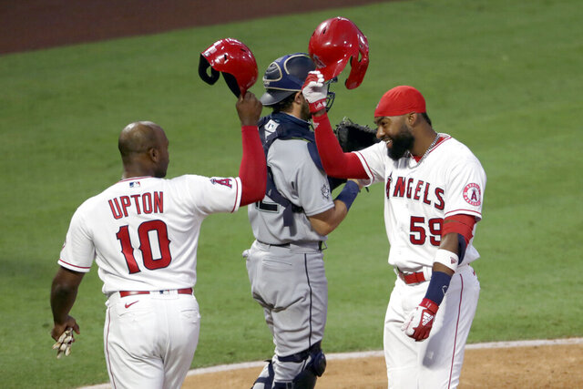 Los Angeles Angels' Jo Adell, right, celebrates his two-run home run with Justin Upton at the plate, next to Seattle Mariners catcher Austin Nola dduring the third inning of a baseball game in Anaheim, Calif., Saturday, Aug. 29, 2020. (AP Photo/Alex Gallardo)