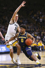 Michigan guard David DeJulius (0) drives the ball around Iowa guard Joe Wieskamp (10) during the first half of an NCAA college basketball game Friday, Jan. 17, 2020, in Iowa City, Iowa. (Rebecca F. Miller/The Gazette via AP)