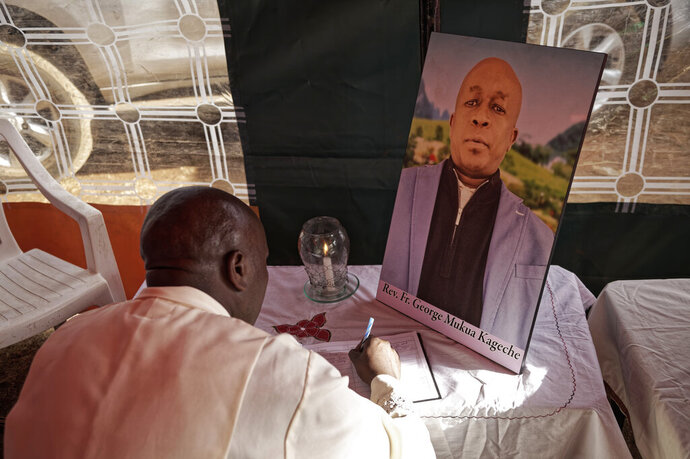 In this photo taken Thursday, March 14, 2019, Father Michael Wa Mugi lights a candle and signs the book of condolence next to a photo of Catholic priest Rev. George Mukua Kageche, 40, who died in the recent plane crash in Ethiopia, at a prayers ceremony held at his home in Githunguri, near Nairobi, in Kenya. The Rev. George Kageche Mukua was one of 32 Kenyans killed when Ethiopian Airlines flight 302 faltered shortly after takeoff from Addis Ababa and crashed, a numbingly high toll on a flight carrying people from 35 countries. (AP Photo/Sayyid Abdul Azim)