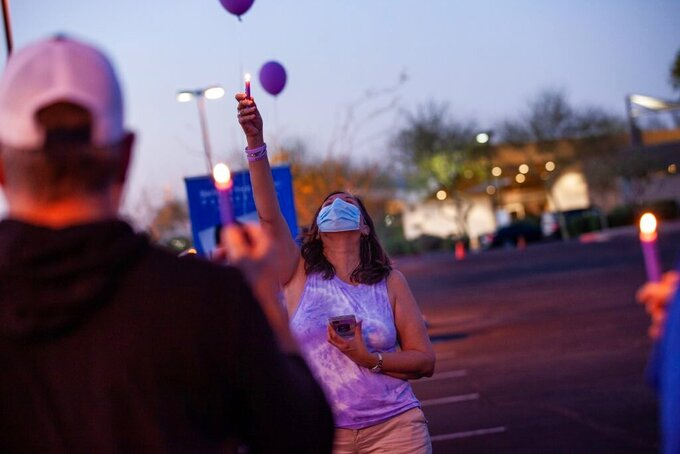 Theresa Guerrero, of Tucson, Ariz., raises a candle in memory of those lost to drug overdoses during an event in Gilbert, Ariz., on March 31, 2021. Her son died of a fentanyl overdose last May, and she says his struggles with drugs were exacerbated by isolation brought on by the pandemic. (Alberto Mariani/Cronkite News via AP)