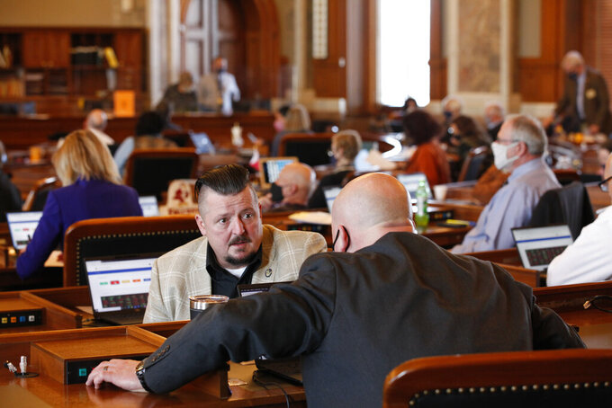 Kansas state Rep. Bill Sutton, left, R-Gardner, confers with Rep. Adam Thomas, right, R-Olathe, as the House debates a proposed anti-abortion amendment to the Kansas Constitution, Friday, Jan. 22, 2021, at the Statehouse in Topeka, Kan. The debate came on the 48th anniversary of the U.S. Supreme Court's historic 1973 Roe v. Wade decision legalizing abortion nationwide. (AP Photo/John Hanna, Pool)