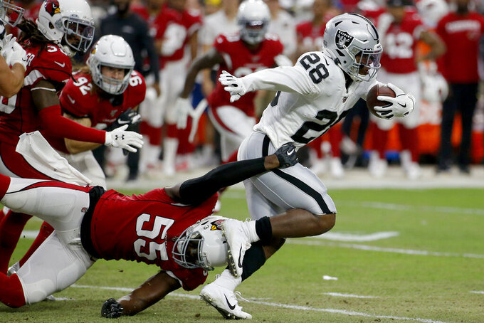 Oakland Raiders running back Josh Jacobs (28) runs aArizona Cardinals linebacker Chandler Jones (55) defends during the first half of an an NFL football game, Thursday, Aug. 15, 2019, in Glendale, Ariz. (AP Photo/Rick Scuteri)