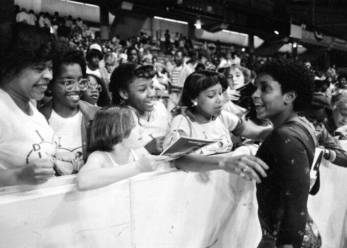 FILE - In this June 5, 1983, file photo, Dianne Durham, right, of Gary, Ind., gives autographs after winning the women's title at the McDonald's U.S.A. Gymnastic Championships at the University of Illinois in Chicago. Durham, the first Black woman to win a USA Gymnastics national championship, died on Thursday, Feb. 4, 2021, She was 52. (AP Photo/Lisa Genesen, File)