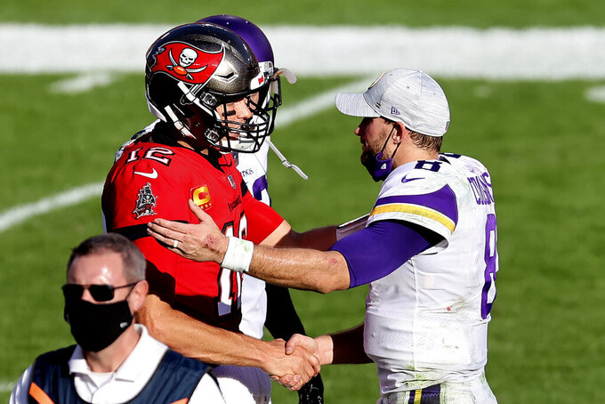 Tampa Bay Buccaneers quarterback Tom Brady (12) shakes hands with Minnesota Vikings quarterback Kirk Cousins (8) after an NFL football game Sunday, Dec. 13, 2020, in Tampa, Fla. (AP Photo/Mark LoMoglio)