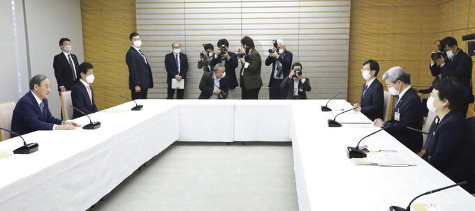 Japanese Prime Minister Yoshihide Suga, left, holds a meeting with Toshiko Fukui, right, president of the Japanese Nursing Association, and Toshio Nakagawa, second from right, president of the Japan Medical Association, at his office in Tokyo on April 30, 2021. Some nurses in Japan are incensed at a request from Tokyo Olympic organizers to have 500 of them dispatched to help out with the games. They say they're already near the breaking point dealing with the coronavirus pandemic.  (Toshiyuki Matsumoto/Kyodo News via AP)